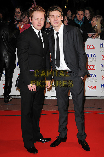 CHARLIE CLEMENTS & CHARLIE G. HAWKINS .The 15th National Television Awards held at the O2 Arena, London, England..January 20th, 2010.NTA NTAs full length black suit grey gray hands in pockets .CAP/CAS.©Bob Cass/Capital Pictures.