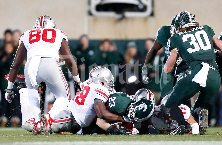 Michigan State Spartans linebacker Chris Frey (23) recovers a loose pall on a Michigan State Spartans punt in the first quarter of the college football game between the Ohio State Buckeyes and the Michigan State Spartans at Spartan Stadium in East Lansing, Saturday night, November 8, 2014. (The Columbus Dispatch / Eamon Queeney)