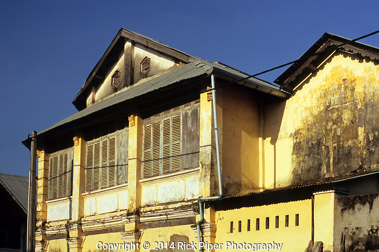 Weathered decaying wooden shuttered facade of old French colonial building in the centre of Kampot, Cambodia.