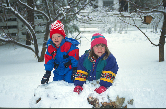 Boy and girl making snow man