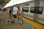 Merrick, New York, U.S. - July 14, 2014 - During evening rush hour, a man walks with his bicycle on elevated platform to board train at Merrick train station of Babylon branch, after MTA Metropolitan Transit Authority and Long Island Rail Road union talks deadlock, with potential LIRR strike looming just days ahead.