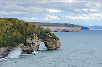 An autumn view of the Pictured Rocks National Lakeshore with a Lake Superior wave crashing into the cliffs. Munising, MI