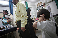 Omar, four-years-old, reacts covering his ears as he looks to a child crying while is getting medical treatment at the emergency ward of the Dar Al-Shifa hospital. Fatimah (at the bottom), his mother, tries to calm down Rashed, Omar's sister. September 25, 2012.