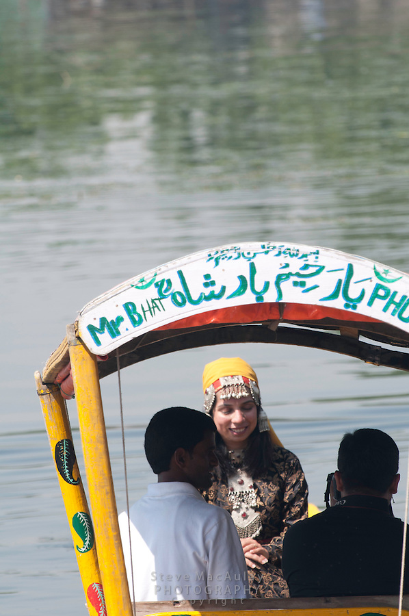 Indian woman in traditional Kashmiri clothing posing for pictures on Dal Lake, Srinagar, Kashmir, India.