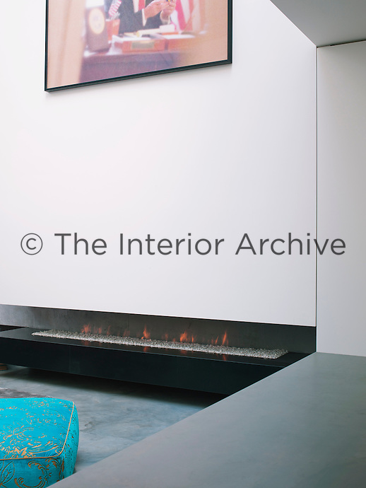 The minimal slot fireplace in the seating area is elevated on a slab above the floor, creating a dramatic detachment of the wall above from the concrete floor below