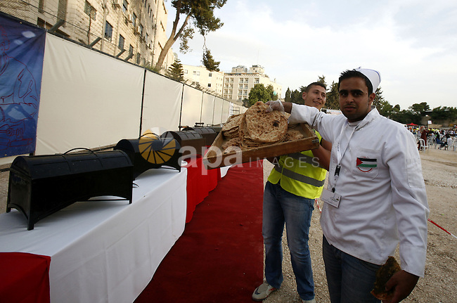 A chef carries a tray of leavened bread garnished with thyme as he and others prepare the longest buffet of natural and organic food which registered a new Guinness world record, on May 26, 2012 in Arab east jerusalem. The Palestinian banquet, prepared by Jerusalem locals, measured 202 metres. Photo by Mahfouz Abu Turk