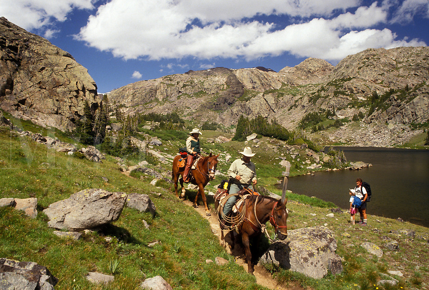 AJ3552, Bighorn National Forest, Wyoming, horseback riding, Bighorn Mountains, Two rangers on horseback ride by mother and daughter hiking in the Cloud Peak Wilderness Area in Bighorn National Forest in the state of Wyoming.