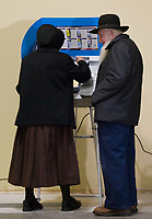 An older Amish couples uses an electronic voting machine at their precinct in the lumber store in Charm, Ohio, Tuesday, Nov. 7, 2006. This was the first election in Ohio where voters had to present a form of identification before voting and the first time all precincts used electronic voting machines.