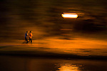 Two people run along a path near the canal in Utrecht, the Netherlands during the evening.