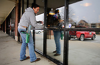NWA Media/DAVID GOTTSCHALK - 12/8/14 - Penni Cannady, with Mr. T's Window Cleaning of Siloam Springs, cleans the edges of windows at Slim Chickens Restaurant at Spring Creek Center in Fayetteville Monday December 8, 2014. Cannady was working with Angela Catron on the job.