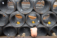 A worker rests among rolls of steel wire at a steel wholesaler market in Shanghai, China..06 Nov 2007