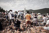 Faithful praying around the statue of the Virgin Mary, named locally as the 'Gospa' on the top of the Podbro, the hill of the apparitions. The exceptional heat wave (Charon) made temperature hit 41&deg;C.<br /> Bijakovici, Medjugorje, Bosnia and Herzegovina.