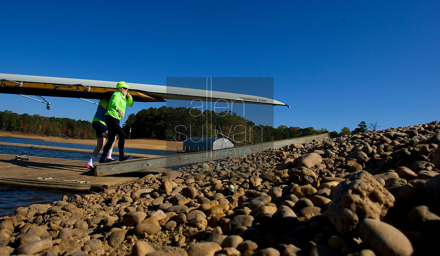 Jack Quigley (front) and Kim Johnson help carry a boat up an exposed section of lake bed at the Lake Lanier Rowing Club. Quiqley said low water levels have altered previously safe rowing routes on the lake.