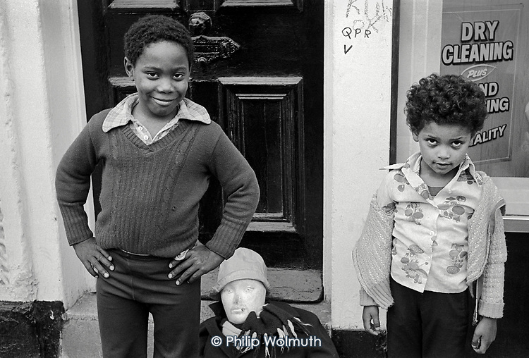 1977: two boys with a Guy collect money for fireworks night, Portobello Road, Notting Hill.