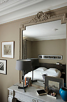 The ornate plasterwork frame around the 19th century mirror has been painted the same flat taupe colour as the walls of this contemporary bedroom