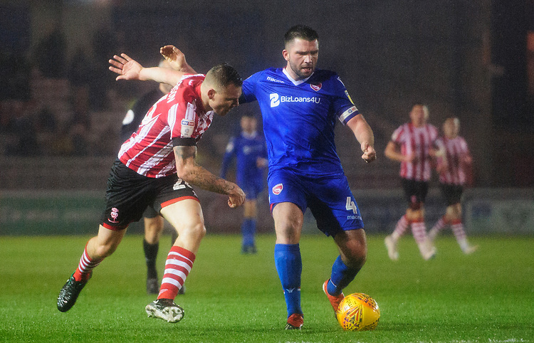 Lincoln City's Harry Anderson vies for possession with Morecambe's Alex Kenyon<br /> <br /> Photographer Chris Vaughan/CameraSport<br /> <br /> The EFL Sky Bet League Two - Saturday 15th December 2018 - Lincoln City v Morecambe - Sincil Bank - Lincoln<br /> <br /> World Copyright © 2018 CameraSport. All rights reserved. 43 Linden Ave. Countesthorpe. Leicester. England. LE8 5PG - Tel: +44 (0) 116 277 4147 - admin@camerasport.com - www.camerasport.com