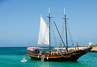 The Jolly Pirates Aruba sailing ship waits in the waters of Aruba's Malmok beach, on the west coast of Aruba. The Jolly Pirates ferries island visitors to some of the island's best snorkling spots, where they can explore underwater life right off the ship. Aruba remains a popular tourist destination, with international planes and cruise ships arriving daily. Aruba, part of the Lesser Antilles, is famous for its white sand beaches, blue/green waters and mild climate.