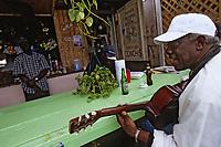 Iles Bahamas / New Providence et Paradise Island / Nassau: un pécheur bahamien joue de la guitare dans un restaurant de rue Marché de Potter's Cay sous le pont de Paradise Island // Bahamas Islands / New Providence and Paradise Island / Nassau: Bahamian fisherman plays guitar at street restaurant Potter's Cay market under Paradise Island bridge