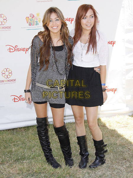 "MILEY CYRUS & BRANDI CYRUS.The 20th annual ""A Time for Heroes"" Celebrity Carnival benefiting Elizabeth Glaser Pediatric AIDS Foundation held at Wadsworth Theater on the Veteran Administration Lawn in West Los Angeles, California, USA. .June 7th, 2009.full length black knee high boots grey sparkly gray silver dress tassels belt chains necklace white top skirt sisters siblings family .CAP/DVS                                                  .©Debbie VanStory/Capital Pictures."