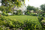 In the early morning light, a small, circular backyard lawn behind the farmhouse on this property is surrounded by a Sissinghurst-style white garden containing white peonies, bleeding heart, delphiniums, white iris, white roses, and garden flox, among others.  The white-painted greenhouse was salvaged from a local arboretum and restored for use here, and adds to the romantic, cottage garden feel. Garden design by Toni Christianson, Christianson's Nursery
