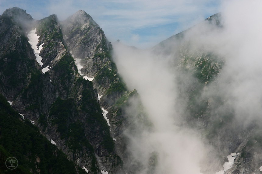 The jagged peaks of the Kaerazu no Ken mountains in the Hida Mountains, catching cloud. Nagano, Japan.