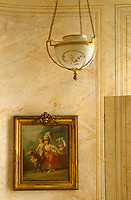 A gilded pendant light hangs above an 18th century painting on a marbleised wall with a concealed door