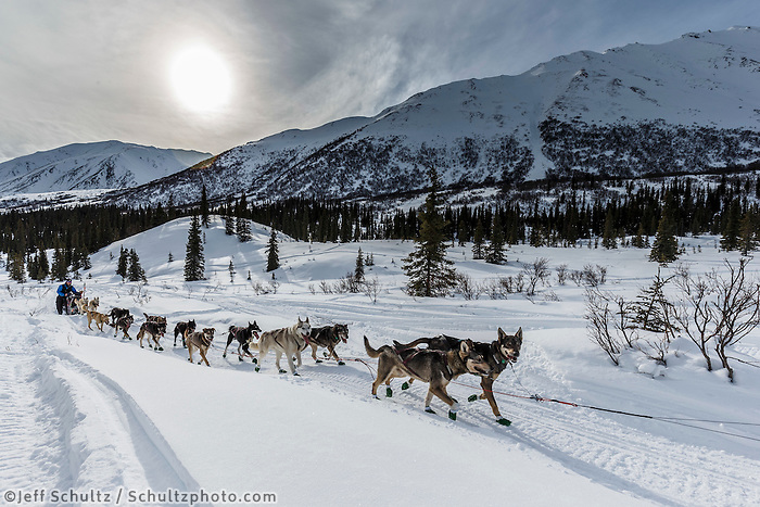 Noah Burmeister runs up hill after leaving Puntilla Lake and the Rainy Pass Checkpoint during Iditarod 2016.  Alaska.  March 07, 2016.  <br /> <br /> Photo by Jeff Schultz (C) 2016 ALL RIGHTS RESERVED