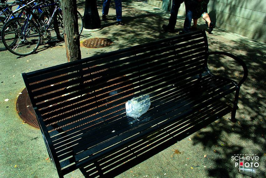 Plastic bag trash on a park bench.