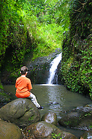 A young boy (age 9) stops to reflect on scenic Maunawili Falls along  the Maunawili hikiking trail, windward Oahu.