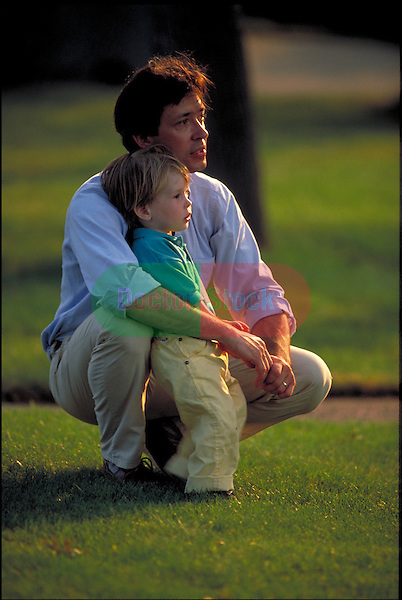 man kneeling in park with toddler child