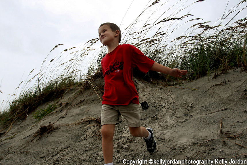 KELLY JORDAN/The Times-Union--082008--Ben Respess, 4, of Jacksonville, feels the breeze hit him as he runs down a dune at the entrance to Jacksonville Beach as Jacksonville feels the effects of Tropical Storm Fay Wednesday afternoon, August 20, 2008.(The Florida Times-Union, Kelly Jordan)