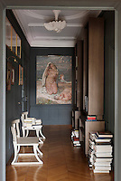 Slim bookcases made of bog oak line one wall of the entrance hall which is dominated at one end by a large oil painting once destined for Le Pavilion Dauphine