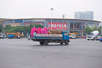 Daytime landscape view of a utility truck carrying plastic chairs near the Qiao Jia Men in the Èrqī Qū of Zhengzhou in Henan province.  © LAN