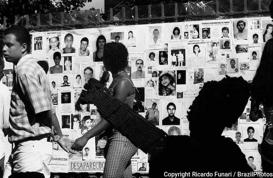 Demonstration for peace in downtown Rio de Janeiro, Brazil in 2000. Mural made of pictures of missing people in Brazil. In the foreground, sculpture made of bullets.