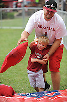 NWA Democrat-Gazette/ANDY SHUPE<br /> Dalton Steed helps his nephew, Finton Ratcliff, 2, both of Prescott, to throw a large bean bag into a hole Saturday, Sept. 5, 2015, while tailgating outside Razorback Stadium in Fayetteville before the University of Arkansas' football game with the University of Texas at El Paso. Visit nwadg.com/photos to see more from the game.