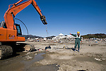 A worker directs a crane that is  clearing up a blocked estuary in the heavily struck city of Rikuzentakata, Iwate Prefecture, Japan on 5 April 20011..Photographer: Robert Gilhooly