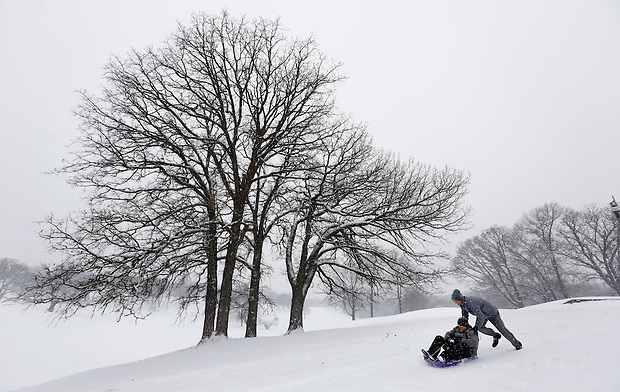 Casey Baney pushes friend Casey Downing on a toboggan to give him a start at the top of a hill while sledding with friends Tuesday, February 4, 2014 at Waveland Golf Course in Des Moines.  Both men, from Des Moines, left work early to have some fun in the snow.