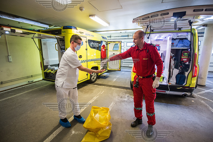 A paramedic is helped cleaning his hands by a colleague. Paramedics in the city of Drammen wearing personal protective equipment (PPE) while transporting patients during the Covid-19 , coronaviraus, pandemic.<br /> <br /> <br /> ©Fredrik Naumann/Felix Features