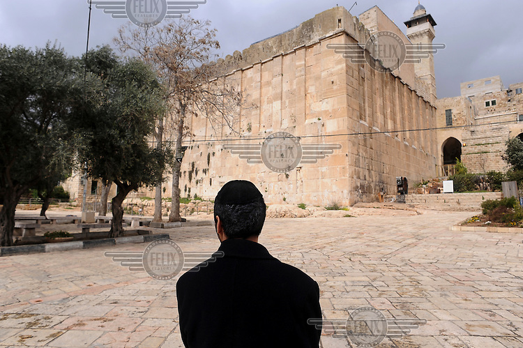 A Jewish man next to the Tomb of the Patriarchs, as he participates in the annual parade marking the Jewish holiday of Purim, in the divided West Bank town of Hebron. Purim is a celebration of the Jews' salvation from genocide in ancient Persia, as recounted in the Book of Esther....