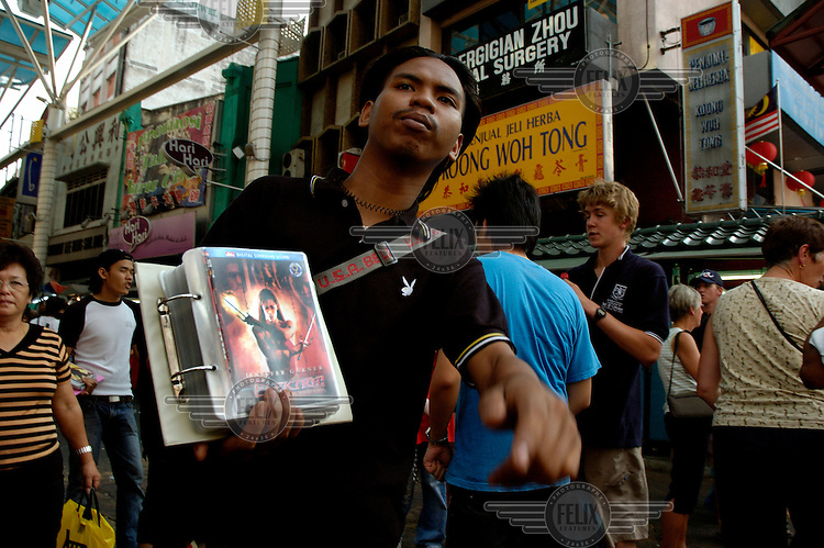 Man openly selling counterfeit Hollywood movies on DVD and music CDs at Jalan Petaling Chinatown market.