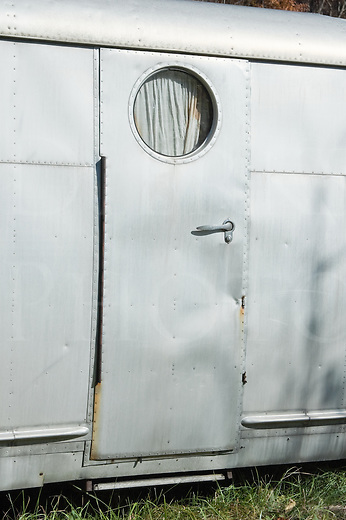 Silver mobile home trailer door with round porthole window, 1950's style, abandoned, old, worn, and dented.