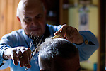 Barber Francesco Oggiano (77 years old) posing while working in his shop in via Sant'Apollinare, Sassari