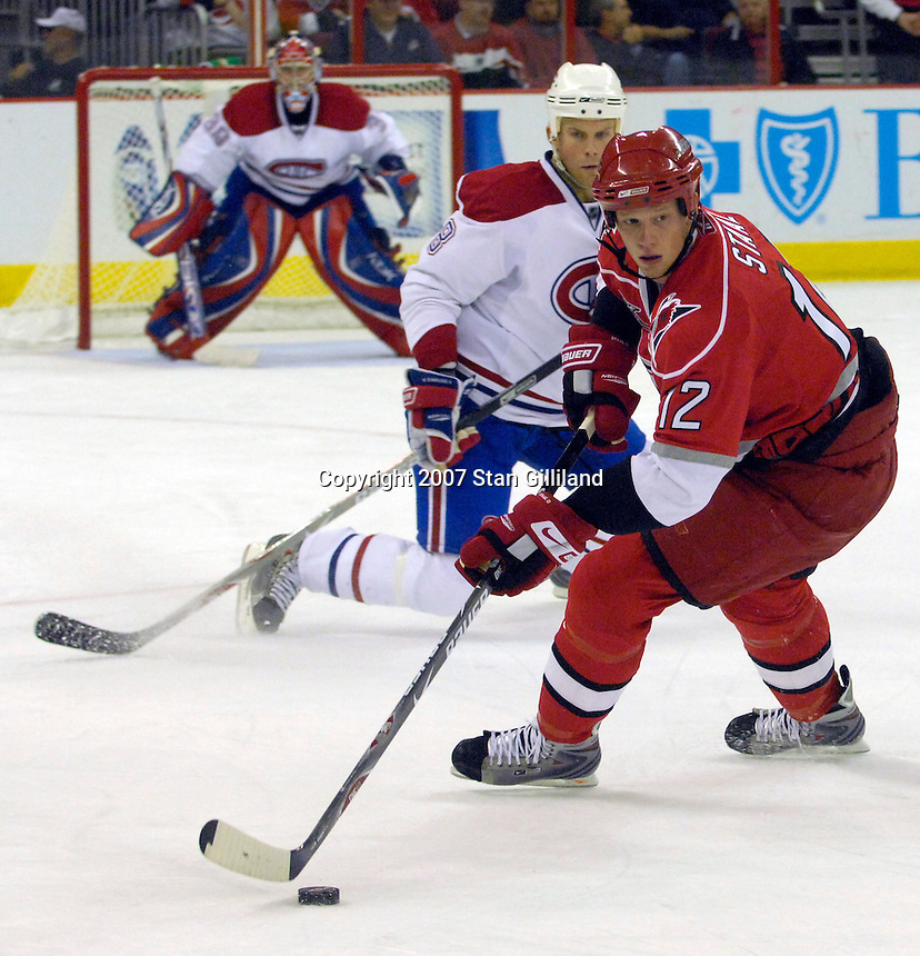 Montreal Canadiens' Michael Komisarek (8) watches as the Carolina Hurricanes Eric Staal (12) turns on the puck during their game Friday, Oct. 26, 2007 in Raleigh, NC. The Canadiens won 7-4.