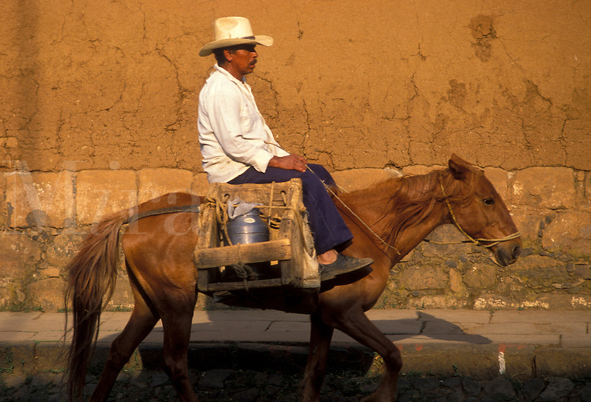 AJ1875, Mexico, horse, Patzcuaro, Mexican man riding a horse carrying goods through the streets of Patzcuaro in the state of Michoacan.