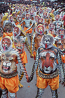 Pulikali performers lined up before prformance at the swaraj road in Trichur, Kerala, India..Pulikali or Kaduvvakali is a two hundred year old folk dance form, practised mostly in Thrissur and Palghat districts of Kerala. It liberally makes use of forms and symbols of nature that finds expression in its bright, bold body painting and high-energy dance movements. The philosophy of Pulikali is that human and nature are integral parts of each other. So by fusing man and beast in its artistic language, it flamboyantly celebrates the connection. Arindam Mukherjee