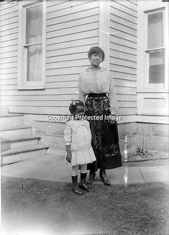 MOTHER AND DAUGHTER. Johnson often traveled throughout the community to take his photographs, but in this case his subjects came to him. This mother in her elegant skirt and the skeptical little girl are standing at the southwest corner of Johnson's house on A Street<br /> <br /> Photographs taken on black and white glass negatives by African American photographer(s) John Johnson and Earl McWilliams from 1910 to 1925 in Lincoln, Nebraska. Douglas Keister has 280 5x7 glass negatives taken by these photographers. Larger scans available on request.