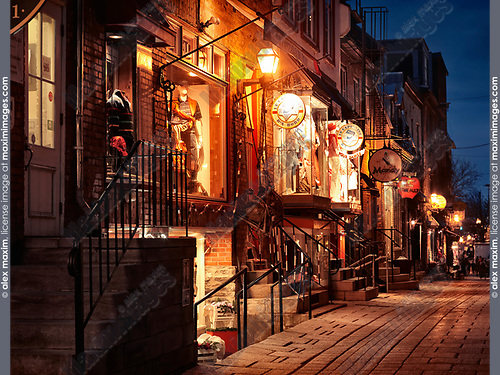 Nighttime view of le Capitaine d'abord, Mandy and other shops and restaurants on a historic street Rue du Petit Champlain in old Quebec City, Quebec, Canada. Ville de Québec.