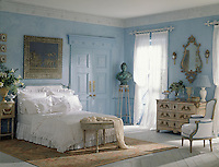 A romantic blue bedroom with a classical theme, with sheer white curtains and a double bed with frilled bed linen. An ornate chest of drawers stands against one wall.