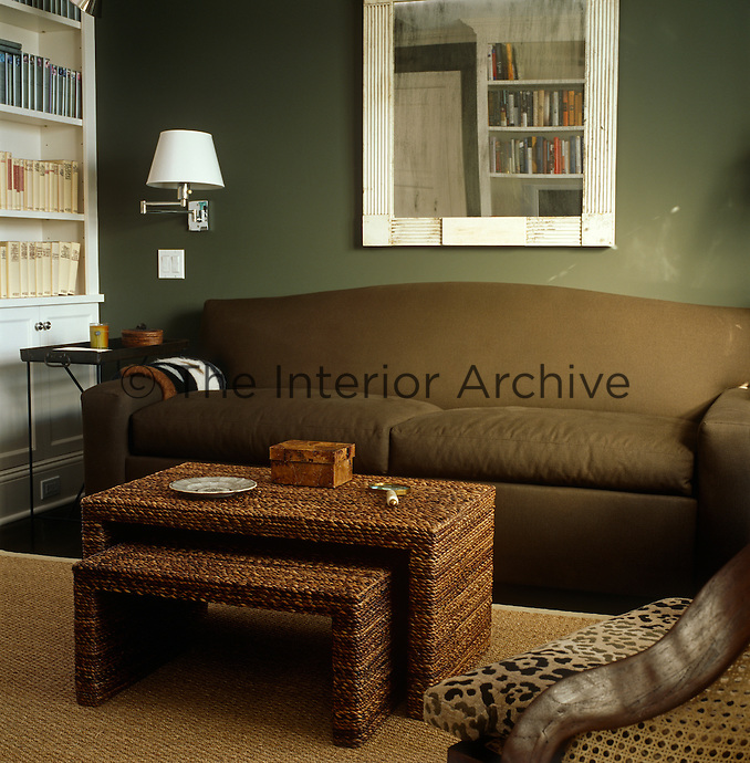 A woven seagrass coffee table and bench are situated in front of a comfortable brown sofa which is set against the khaki green walls of the living room