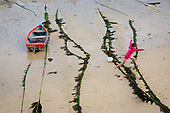 A girl jumps over seaweed encrusted ropes in St.Ives harbour at low tide, Cornwall.